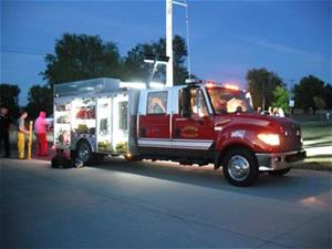 A Larned Fire Engine with lights on at night.